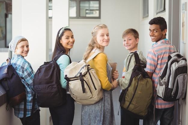 Portrait d'étudiants souriants debout avec ordinateur portable et sac d'école dans le couloir