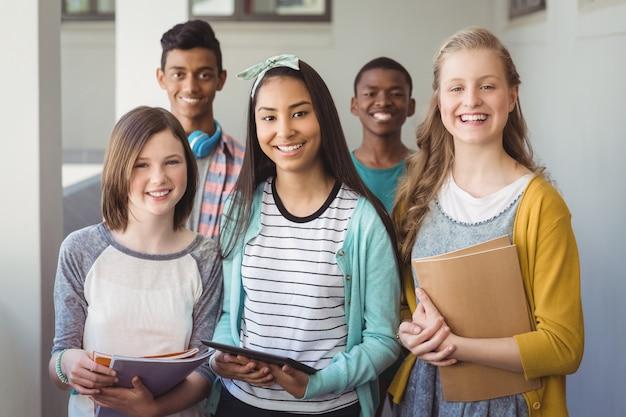 Portrait d'étudiants souriants debout avec tablette numérique et ordinateur portable dans le couloir