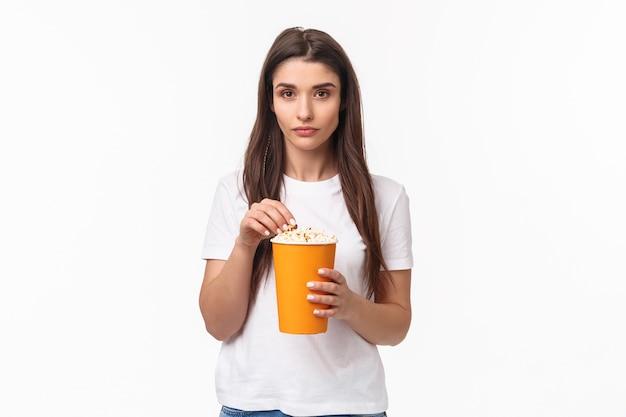 Portrait expressif jeune femme mangeant du pop-corn