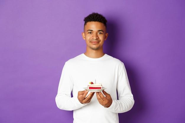 Portrait expressif jeune homme tenant un gâteau
