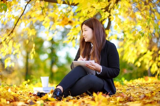 Portrait en extérieur belle étudiante asiatique fille. jeune femme étudiant / travaillant et profitant d'une belle journée d'automne ensoleillée