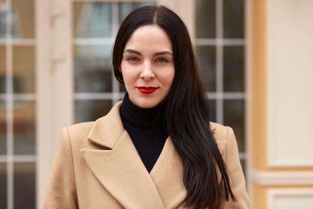 Portrait à l'extérieur de la belle femme aux cheveux foncés près de la fenêtre du bâtiment de la ville. jeune femme brune regarde directement la caméra, a un maquillage léger avec des lèvres rouges, un pull noir habillé, un manteau beige.