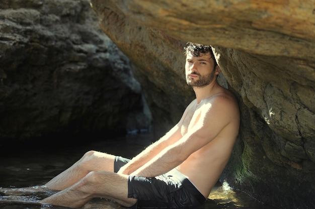 Portrait extérieur de jeune homme élégant près de la mer et des rochers