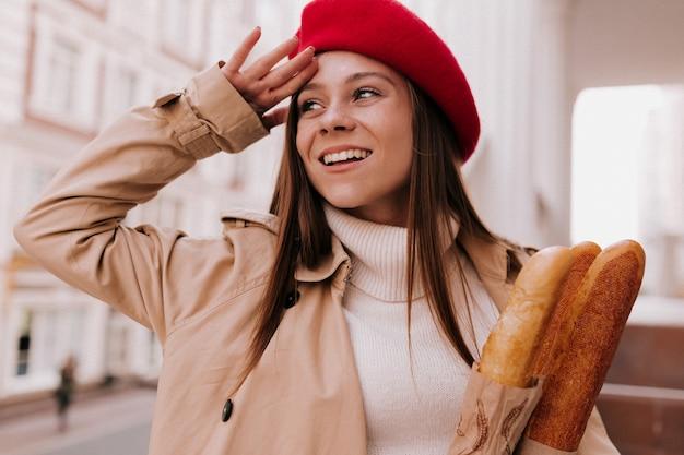 Portrait extérieur de jeune jolie femme française aux longs cheveux brun clair portant un béret rouge
