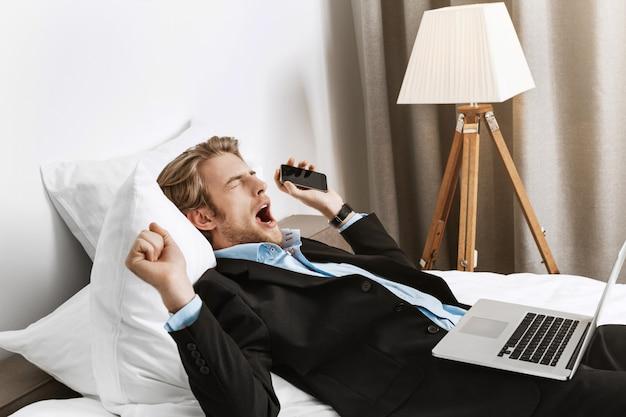 Portrait f homme d'affaires barbu allongé dans une chambre d'hôtel, tenant un téléphone et un ordinateur portable, bâillant et s'endormant après un travail productif.