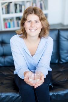 Portrait de face d'un adolescent heureux tenant un verre d'eau vous regardant assis sur un canapé dans le salon de la maison