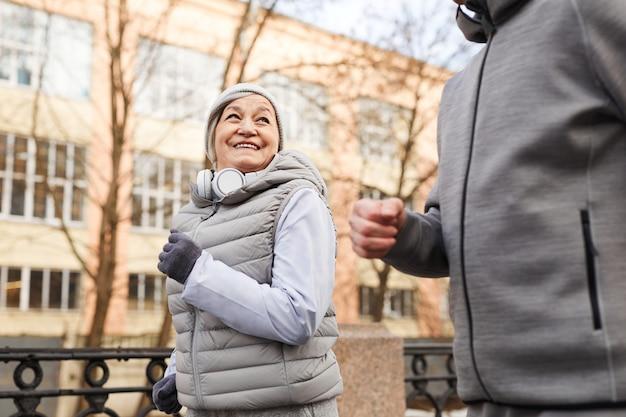 Portrait à faible angle d'un couple de personnes âgées actifs courant à l'extérieur en hiver et souriant joyeusement, espace pour copie