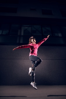 Portrait faible vue verticale de la jeune femme active de mode mince athlétique sautant à bras ouverts dans la rue devant le bâtiment gris la nuit.
