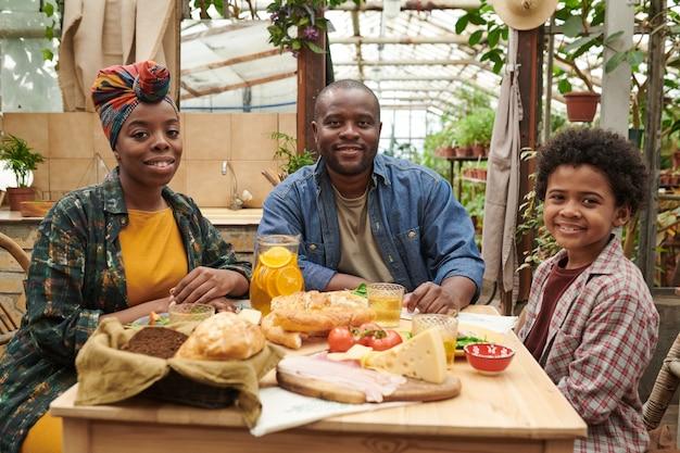 Portrait d'une famille africaine heureuse souriant à la caméra alors qu'il était assis à table à manger pendant l'heure du déjeuner