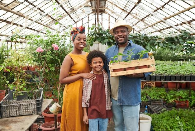 Portrait d'une famille africaine de trois personnes souriant à la caméra et debout dans la serre