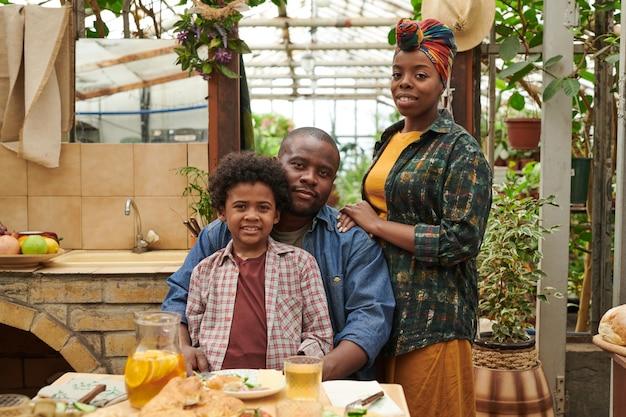 Portrait d'une famille africaine de trois personnes souriant à la caméra pendant le dîner dans le jardin