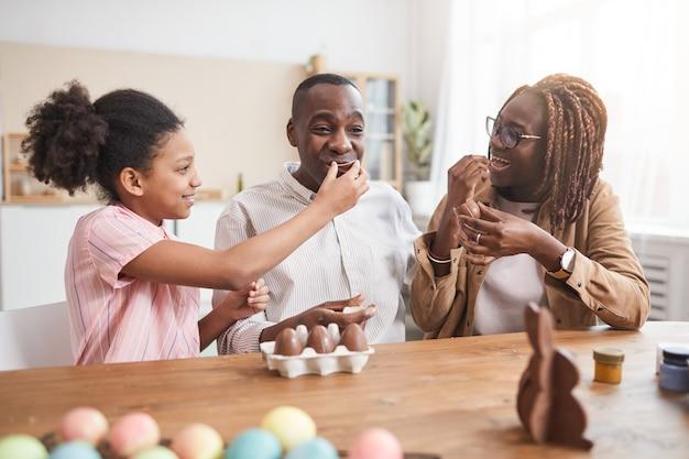 Portrait d'une famille afro-américaine aimante faisant des décorations de pâques au chocolat et les dégustant assis à une table en bois dans un intérieur confortable