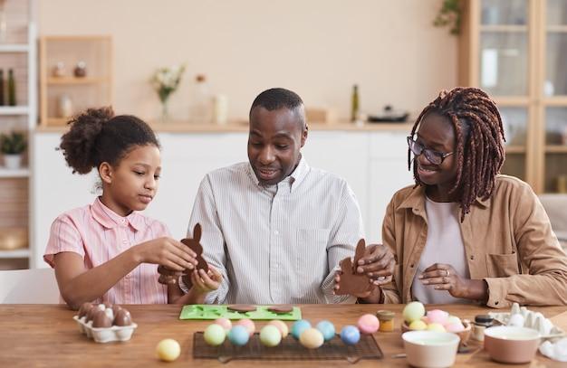 Portrait d'une famille afro-américaine aimante faisant des lapins de pâques au chocolat assis à une table en bois dans un intérieur confortable et profitant des préparatifs des vacances