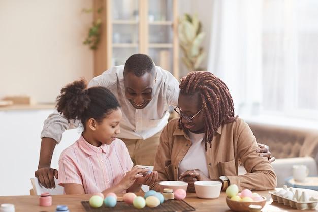 Portrait d'une famille afro-américaine aimante peignant des œufs de pâques ensemble tout en étant assis à une table en bois dans un intérieur confortable et en profitant de l'art du bricolage, de l'espace de copie