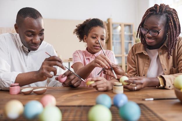 Portrait d'une famille afro-américaine heureuse peignant des œufs de pâques ensemble assis à une table en bois dans un intérieur confortable, décorations de pâques bricolage