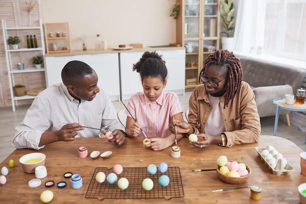 Portrait d'une famille afro-américaine moderne peignant des œufs de pâques ensemble assis à une table en bois dans un intérieur confortable, décorations de pâques bricolage, espace de copie