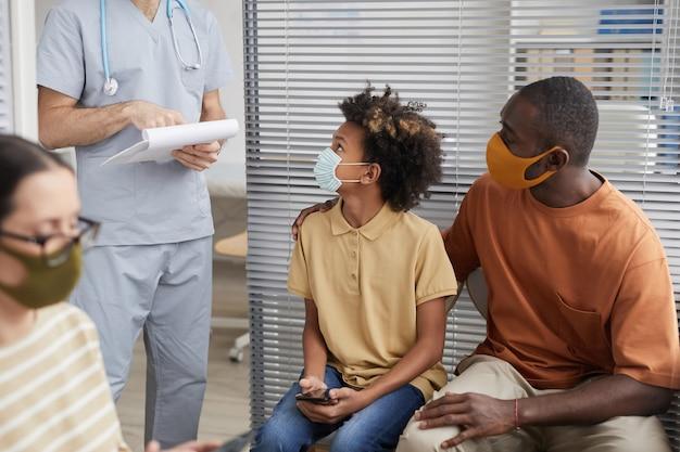 Portrait d'une famille afro-américaine portant des masques et regardant un médecin en faisant la queue à la clinique médicale