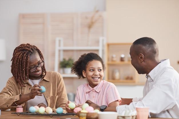 Portrait d'une famille afro-américaine riante peignant des œufs de pâques ensemble tout en étant assis à une table en bois dans un intérieur confortable et en profitant de l'art du bricolage