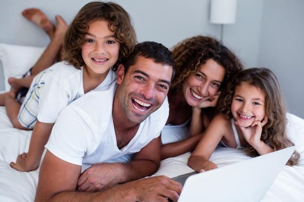 Portrait de famille à l'aide d'un ordinateur portable ensemble sur le lit