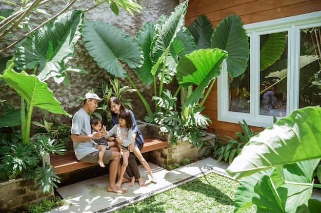 Portrait de famille asiatique profiter de leur temps à l'arrière-cour tropicale à la maison