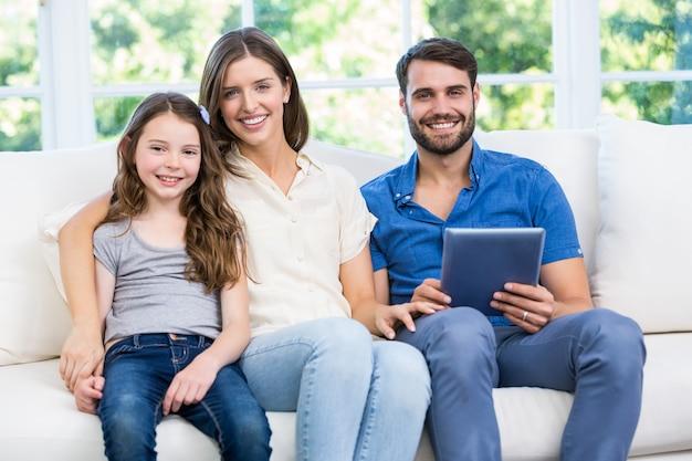 Portrait de famille assis sur un canapé avec tablette numérique