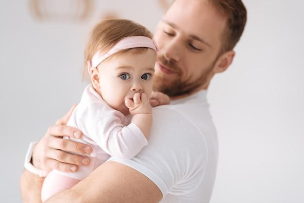 Portrait de famille . bébé fille concentrée chérie vivante couchée dans les mains du jeune père et regarde au loin tout en exprimant la positivité
