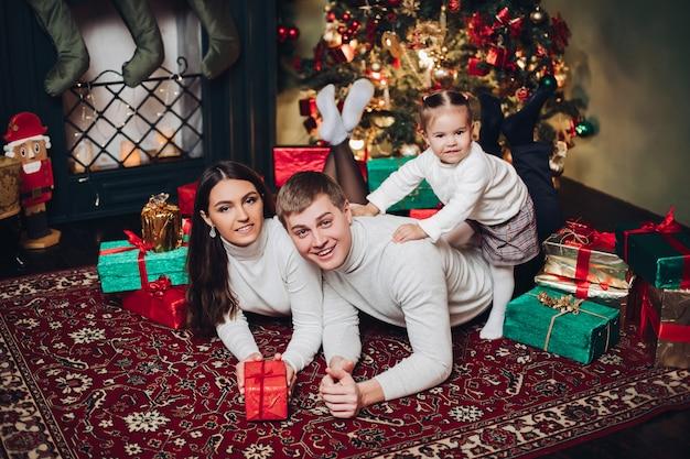 Portrait de famille caucasienne heureuse avec des cadeaux posant à côté de la cheminée.