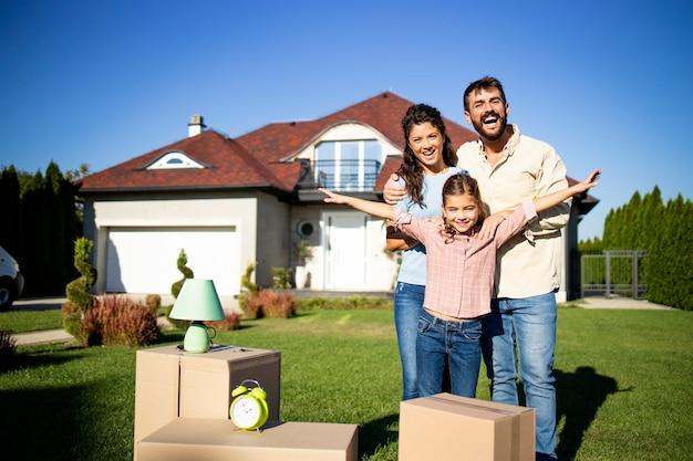 Portrait d'une famille caucasienne heureuse debout devant leur nouvelle maison prête à emménager.
