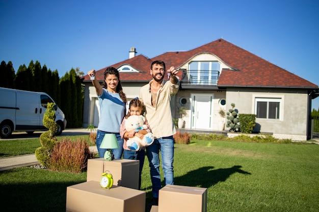 Portrait de famille caucasienne tenant les clés de leur nouvelle maison immobilière.