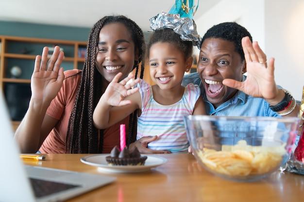 Portrait d'une famille célébrant son anniversaire en ligne lors d'un appel vidéo tout en restant à la maison