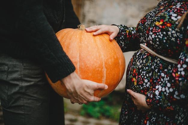 Portrait de famille. charmant couple enceinte pose à l'extérieur