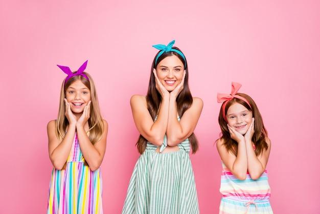 Portrait de famille charmante touchant leurs visages à la recherche avec un sourire à pleines dents portant des robes lumineuses jupe isolé sur fond rose