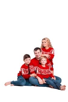 Un portrait d'une famille avec deux enfants avec des vêtements de noël