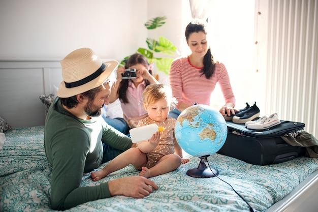 Portrait de famille avec deux petites filles emballant pour des vacances au lit à la maison.