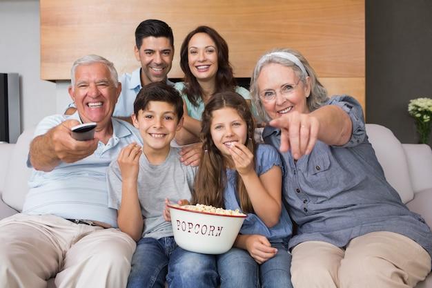 Portrait de famille élargie heureuse devant la télé dans le salon