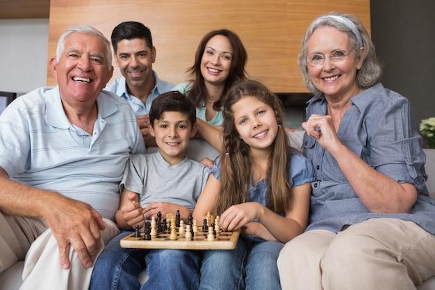 Portrait de famille élargie heureuse jouant aux échecs dans le salon