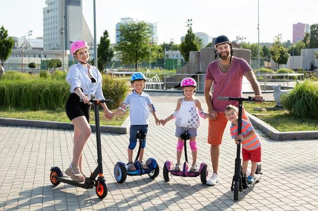 Portrait de famille avec enfants sur des scooters électriques et gyroscope dans le parc en été.