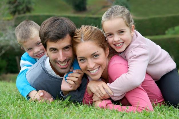Portrait de famille heureuse allongée dans l'herbe