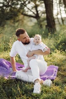 Portrait de famille heureuse au coucher du soleil, passer du temps et jouer dans la nature.
