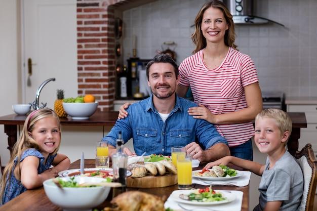 Portrait de famille heureuse ayant un repas dans la cuisine