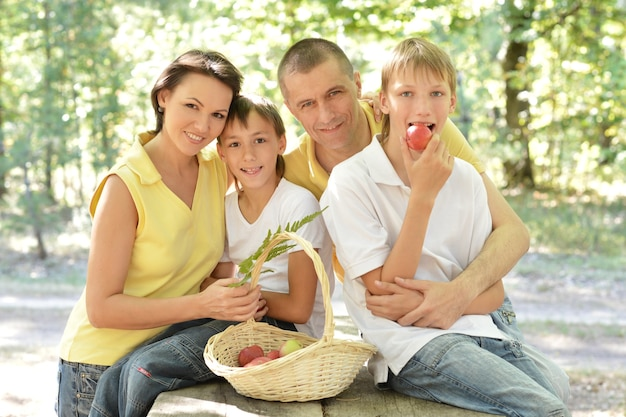 Portrait d'une famille heureuse avec une corbeille de fruits