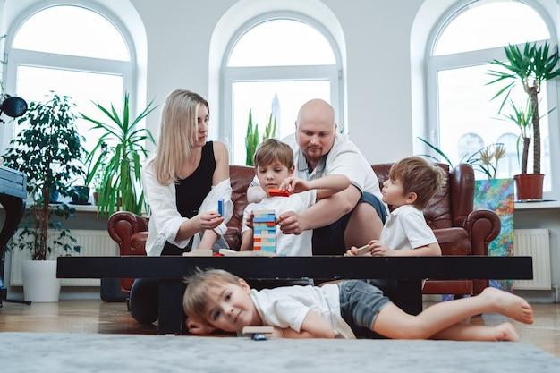 Portrait d'une famille heureuse de couple en relation et de leurs trois enfants, ils jouent ensemble au jeu de jenga à la maison.