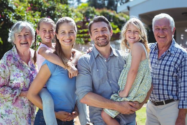 Portrait de famille heureuse, debout dans la cour arrière