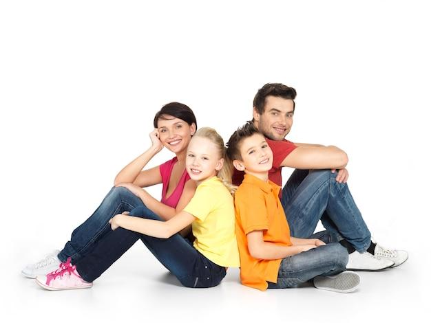Portrait de la famille heureuse avec deux enfants assis au studio sur le sol blanc