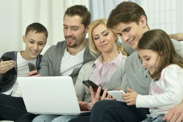 Portrait de famille heureuse avec des gadgets électroniques à la maison