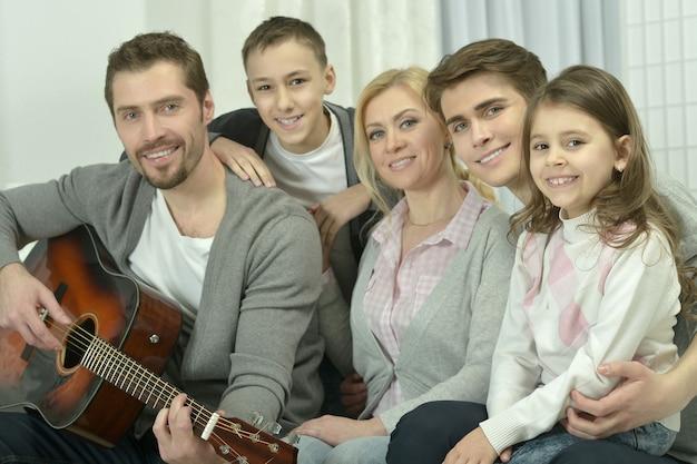 Portrait de famille heureuse avec guitare à la maison