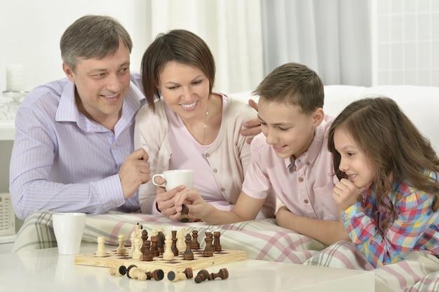 Portrait d'une famille heureuse jouant aux échecs à la maison