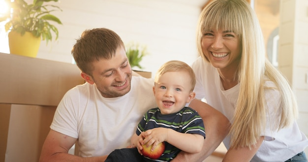 Portrait de famille heureuse à la maison, assis sur le sol et jouant ensemble.