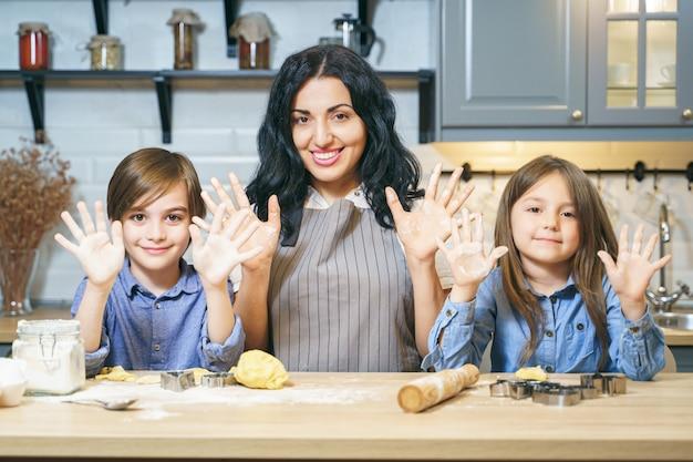 Portrait d'une famille heureuse de maman et de deux enfants montrant les mains et souriant tout en faisant des cookies dans la cuisine