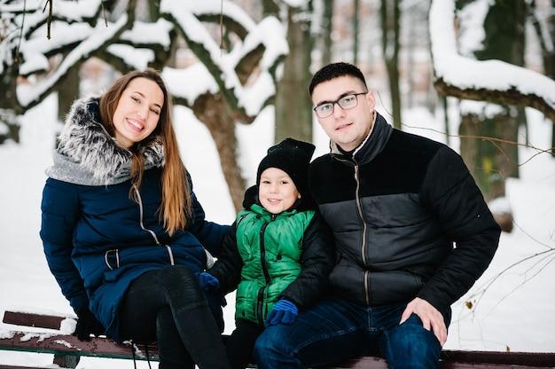 Portrait de famille heureuse marchant dans un parc d'hiver de neige. père, mère et enfants garçon s'amusent et jouent sur une promenade hivernale enneigée dans la nature.